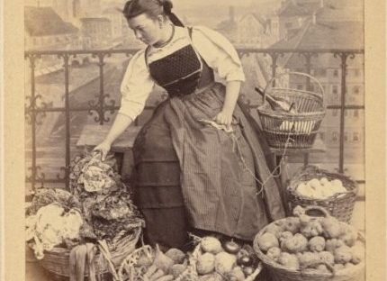 19th century photo of Swiss woman knitting, surrounded by baskets of vegetables.