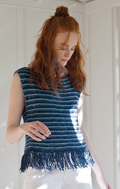 Woman wearing knitted tank top with dark and light blue stripes, and bottom edge lined with tassels