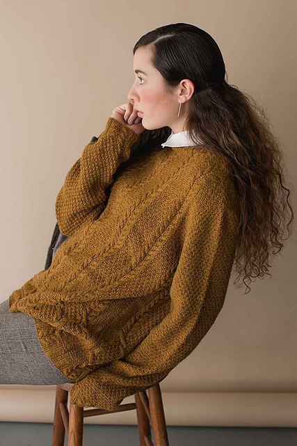 Oversized knitted sweater with cables in ochre yellow.