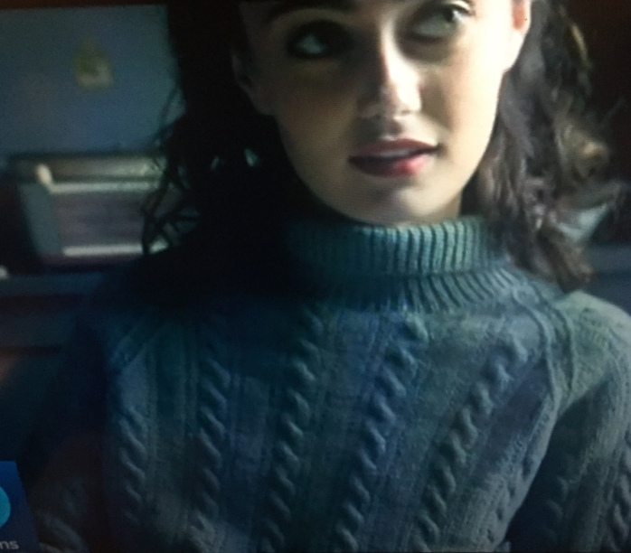 Ella Purnell as Hester Argyll in Ordeal by Innocence (BBC 2018) wearing long, oversized,cabled jumper/sweater.