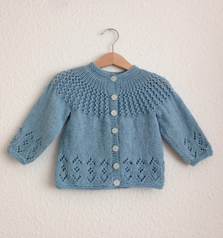 Child's knitted cardigan with pretty lace details.