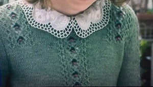 Fitted green cardigan with textured lace panels, worn with neat white, lace collar of blouse