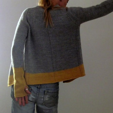 Aran weight, raglan cardigan with thumb openings and contrast colour border at cuffs and hem. Designed by Isabell Kraemer.