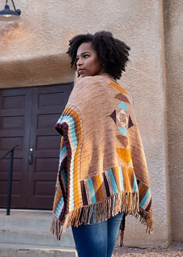 Woman wearing poncho style cardigan with geometric intarsia colour-work details and fringe edging, in warm colours inspired by the American Southwest.