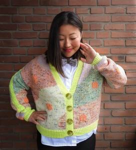 Woman wearing knitted cardigan, made up of multiple, multicoloured intarsia and stranded colour-work shapes and with contrasting neon yellow button band, hem and lace sleeve detail.