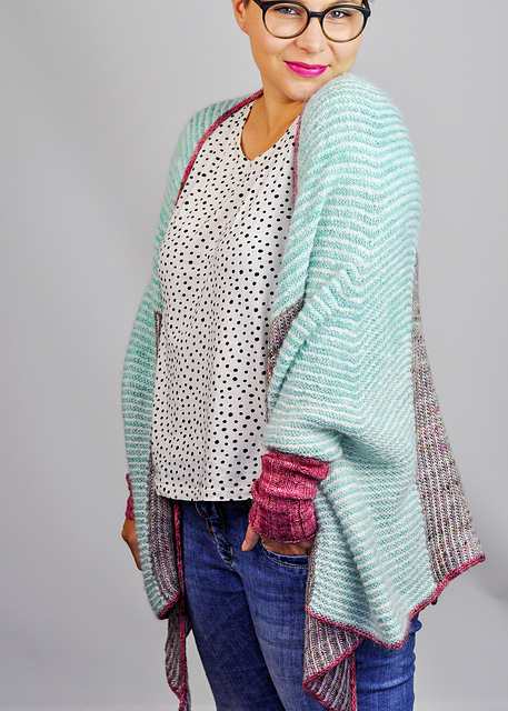 Woman wearing oversized, slouchy shrug, knitted in merino/mohair In multicoloured, striped brioche sections, with contrast colour edging and cuffs.
