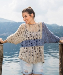 Woman wearing knitted silk/linen blend sweater with all over lace majority of the sweater is a stone colour, but the sleeve and a horizontal stripe across the centre of the body are worked in a contrasting blue grey shade.