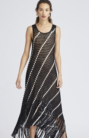 Model wearing black knitted dress from Oscar de la Renta, with all-over lace mesh and slanting contrast white stripe design and tassel hem.