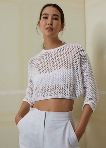 Model wearing cropped, knitted, white mesh sweater with oversized fit and 3/4 sleeves. Knitting pattern by LangYarns Switzerland.