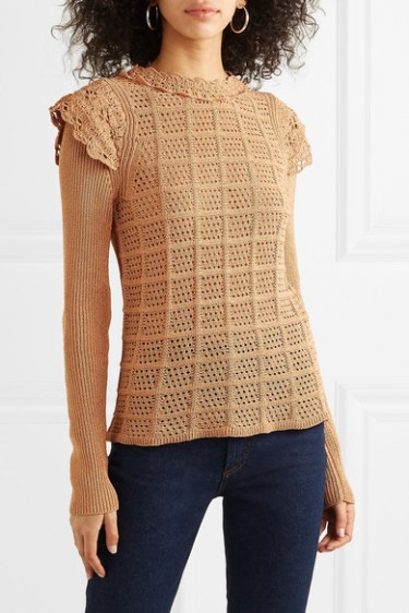 Model wearing knitted, biscuit coloured jumper with pointelle grid front and crochet ruffles at neck and shoulder.