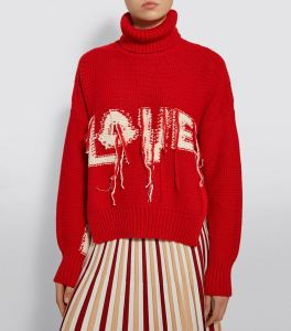 Woman wearing red, roll-neck, knitted sweater with 'love' slogan. The sweater fabric appears to be inside out, with the reverse side of knitting and intarsia lettering exposed and the ends still dangling from the intarsia colour-work.