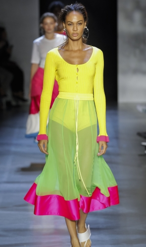 Model wearing bright yellow, scoop neck, knitted cardigan with contrast cuffs in hot pink. Worn with midi length, see through skirt in pale green with hot pink border at hem.