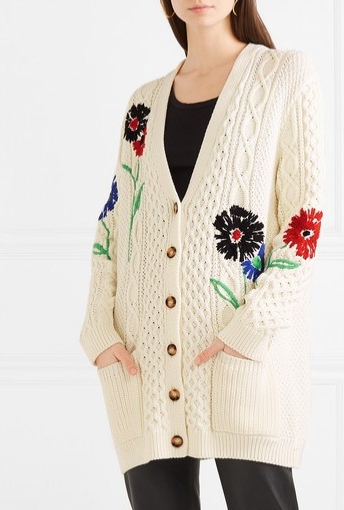 Model wearing cream, oversized, knitted cardigan from REDValentino. There is an all-over cable, textured design and embroidered red, black and blue flower details.