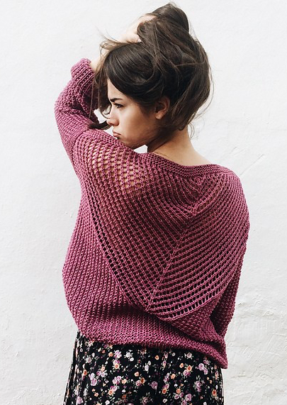 Model wearing knitted sweater with dramatic sweeping triangle of mesh lace across the back.