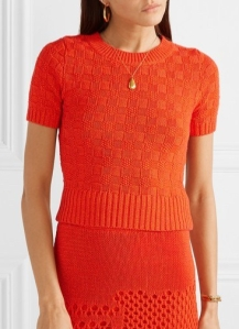 Woman wearing bright orange, short, fitted, knitted top with all-over, chequerboard texture and deep ribbing at hem.