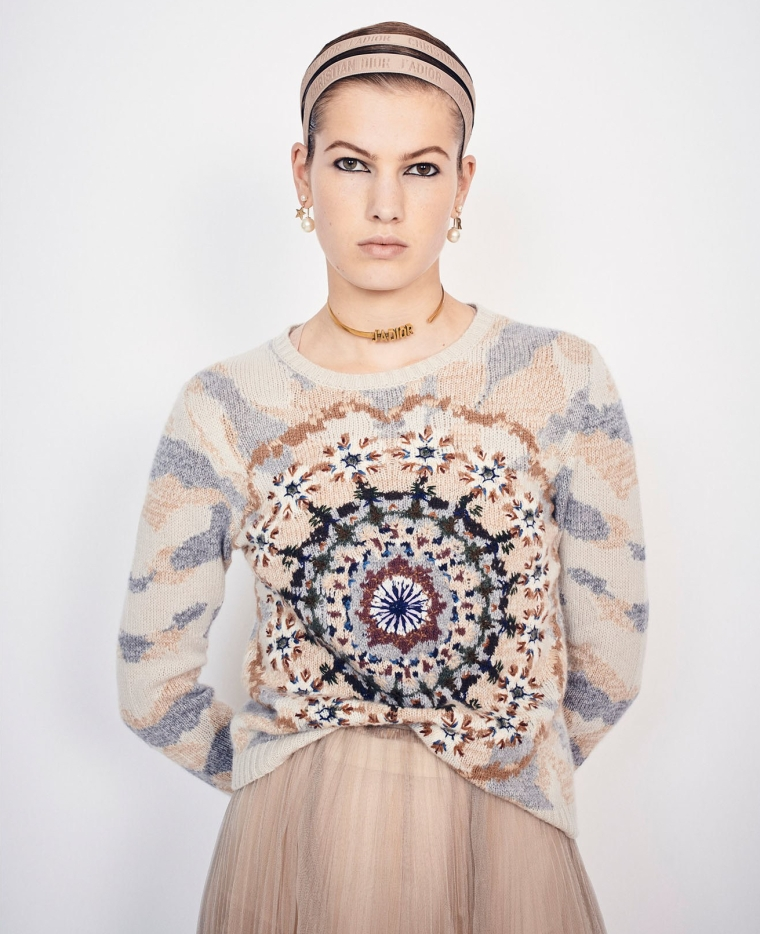 Model wearing Dior summer 2019 collection, including sweater in soft peach, blue and navy colours forming an abstract, kaleidoscope design in intarsia colour-work with embroidery details.