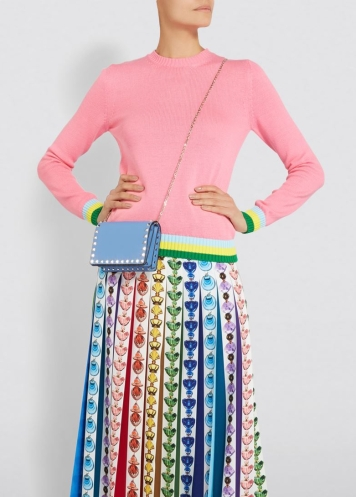 Model wearing knitted, pink sweater with contrasting, green, yellow and blue stripes at cuffs and hem. Worn with multi coloured print, maxi skirt. From Mary Katrantzou, Summer 2019.