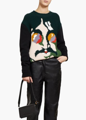 Woman wearing knitted sweater with all-over, multicoloured intarsia design of John Lennon.