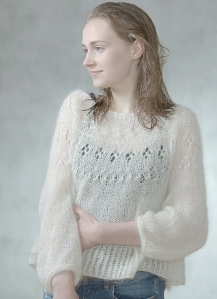 Woman wearing lightweight, knitted, oversized sweater with lace detail across yoke.