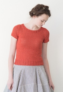 Woman wearing fitted, orange top knitted in linen and with classic crew neck and ribbed border at hem.