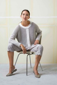 Woman wearing oversized, knitted, cotton sweater in grey with contrasting white neckline and vertical stripe down centre.