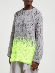Woman wearing oversized, knitted sweater with all-over lace repeats, with the main body and sleeves in grey and third of body fading into neon yellow.