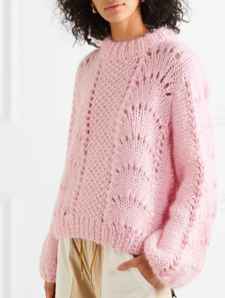 Model wearing pink, chunky knit sweater with panels of fan lace and mesh. Ganni Summer 2019.
