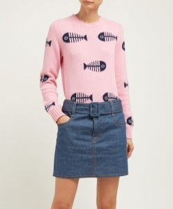 Woman wearing knitted pink jumper with repeated intarsia motif of a fish skeleton in navy.