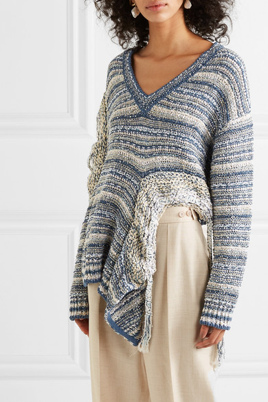 Model wears slouchy, knitted linen cotton sweater with dramatic cutouts and asymmetric hemline. Fabric is mottled blue and white stripes. From Stella McCartney Spring 2019.