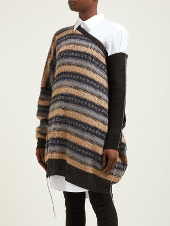 Woman wearing oversized, knitting sweater in stripes of grey, orange and dark brown with stranded colourwork cross design, with one dark brown sleeve, giant cut outs and slouchy fit.