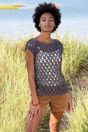 Model wearing knitted cotton, mesh top over shorts on a summer day.