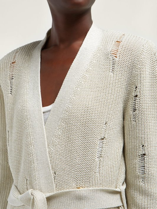 Woman wearing cream, knitted cardigan with faux rips created by lace work.