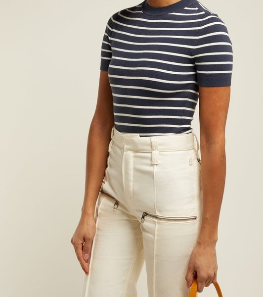 Woman wearing short-sleeved top with crew neck in navy striped with white, made from a stretchy knitted fabric. Worn tucked in to flared white trousers, reminiscent of 1930s daywear.