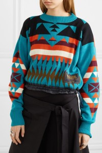 Model wearing knitted jumper with multicoloured, geometric intarsia colour-work design.