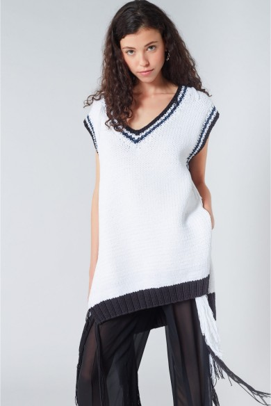 Model wearing oversized, knitted, V-neck tank top in white with black stripes detail at neck and him with tassles at hemline. Sonia Rykiel summer 2019.