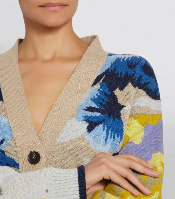 Model wearing knitted, wool cardigan with pale, camel coloured fabric combined with striking, floral intarsia motifs in blues, yellows and greys.