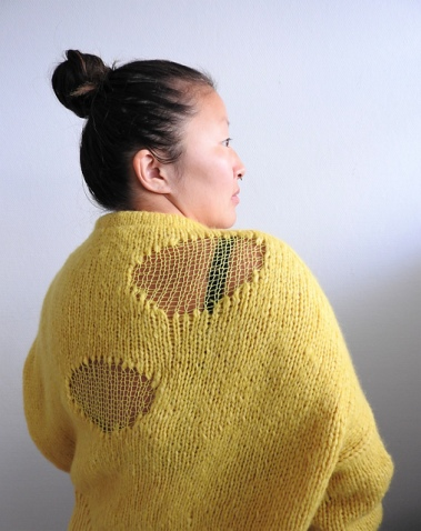 Woman wearing bright yellow, knitted sweater with faux, ripped holes made out of lighter weight yarn.