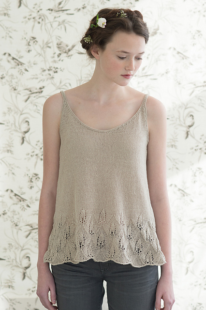 Model wearing pale beige tank top, with scoop neck, knitted in linen, and with pretty lace detail at hem. Pattern by Pam Allen.