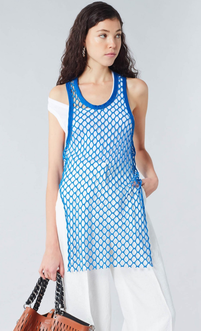 Model wearing Sonia Rykiel Blue, openwork mesh lace tank top over white vest and white, white legged trousers. Summer 2019.