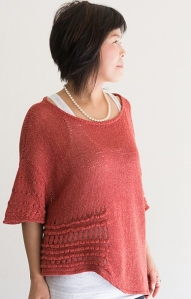 Woman wearing scoop neck, knitted silk/cotton sweater in orange, with dramatic asymmetric hem and textured eyelet sections at sides and bottom of the 3/4 length sleeves.