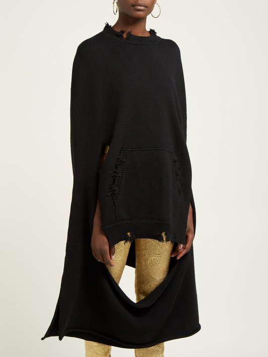 Woman wearing knitted, black sweater or poncho with roughly finished edges, and large cut outs that give distressed finish.