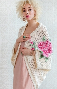 Model wearing oversized, knitted mesh cardigan with large cross-stitch embroidered roses.