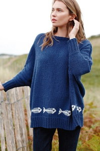 Woman wearing oversized, knitted sweater in dark blue with repeating motif of fish skeletons in white that run above the ribbed hem.