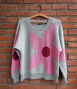 Knitted sweater in pale grey with large, pink and red floral intarsia motif across the front and with similar motifs across the sleeves.