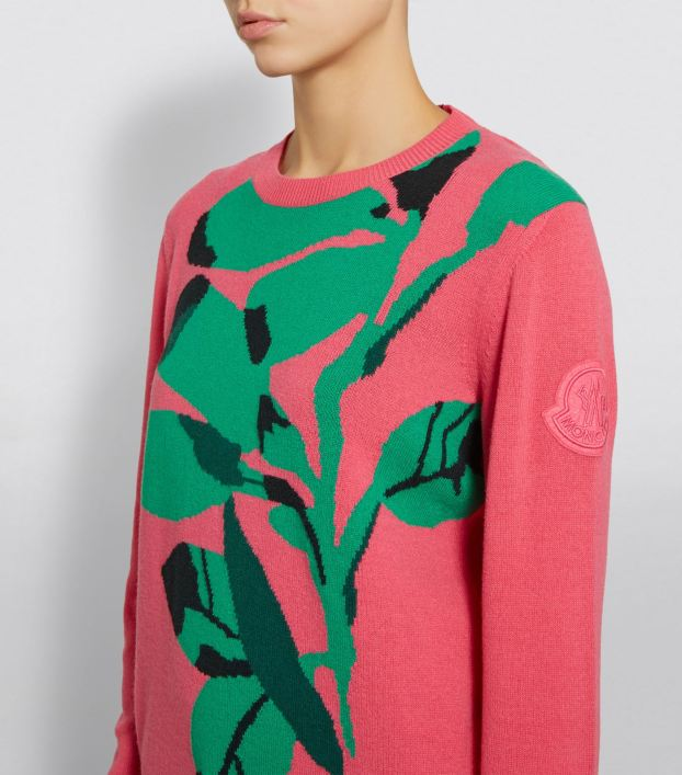 Woman wearing deep pink, knitted sweater with large green, intarsia colour-work motif of a sweep of leaves that covers most of the front.