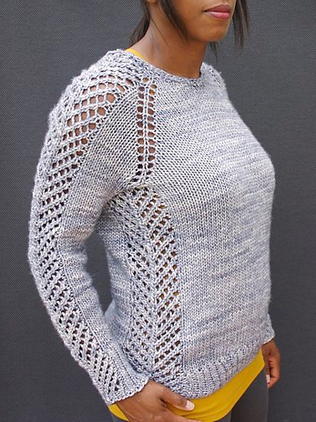 Knitwear designer Jimenez Joseph wearing knitted, crew neck sweater with striking eyelet lace details along side seams, shoulders and sleeves.