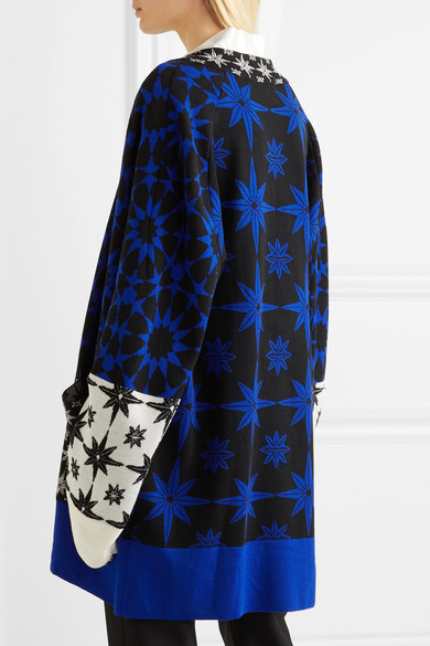 Model wearing long, knitted cardigan with rich intarsia colour-work star designs in shades of blue and with contrast white sleeve detail and blue hem.