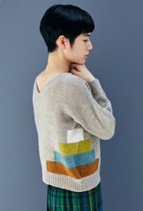 Woman wearing grey, knitted cardigan with multicoloured, rectangle block, intarsia design running across side seams.