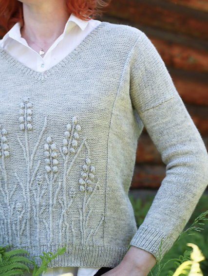 Reverse stocking stitch, knitted sweater with textured floral design.