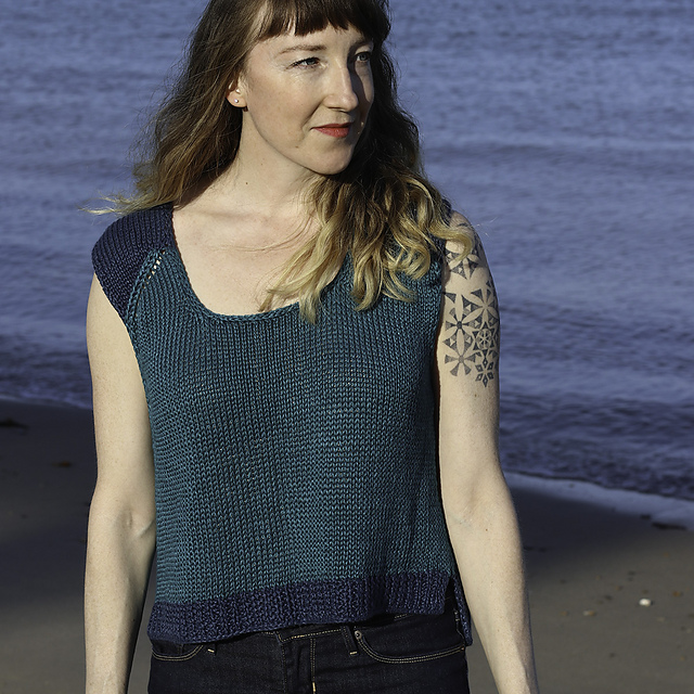 Woman wearing knitted, linen top with short sleeves. Most of the top is in a deep teal shade but the cap sleeves and bottom hem are in a dark blue.